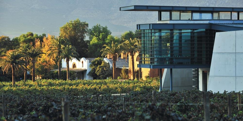 Original Errazuriz casa winery in the background with the new icon winery in the foreground, surrounded by vines