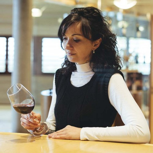Eva de Benito, Head Winemaker of Viña Real in the Rioja Alavesa, stands wearing a black and white top, while examining the colour of a red wine in a glass tilted against a pale wooden counter top