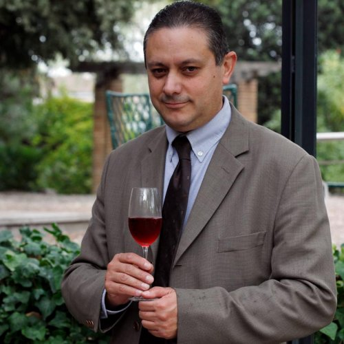 Pedro Muñoz Gómez, Technical Director and Winemaker outside the winery, dressed in business suit, holding a glass of Cava