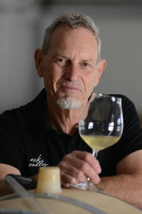 Gordon Russell - Senior Winemaker - dressed in an Esk branded black top, leaning on barrel, examines the progress of white wine ageing - Portrait image