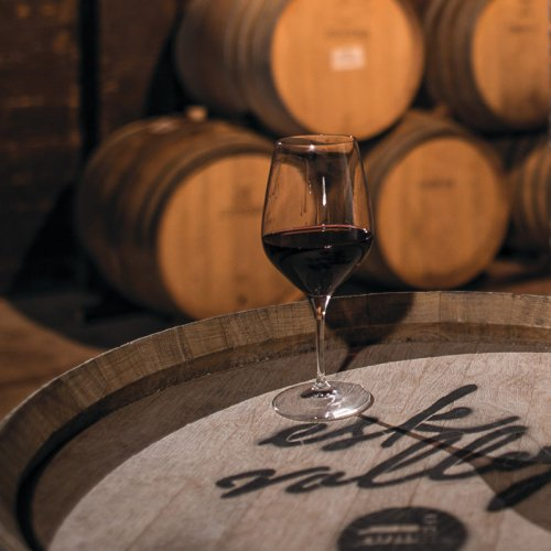 A glass of red wine sits on an Esk Valley branded barrel end in the cellar